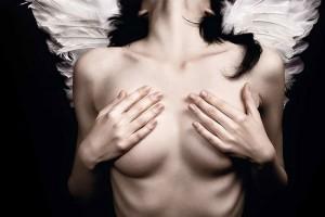 Une femme seins nus avec des ailes d'ange